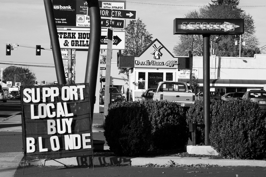 """Support Local"" reads a sign in front of Blondie's Coffee stand. Blondie's is a locally owned, one of a kind espresso shop. In the background you can see the presence of the corporate monopoly called Dutch Bros. To date, there are 137 Dutch Bros. franchises."