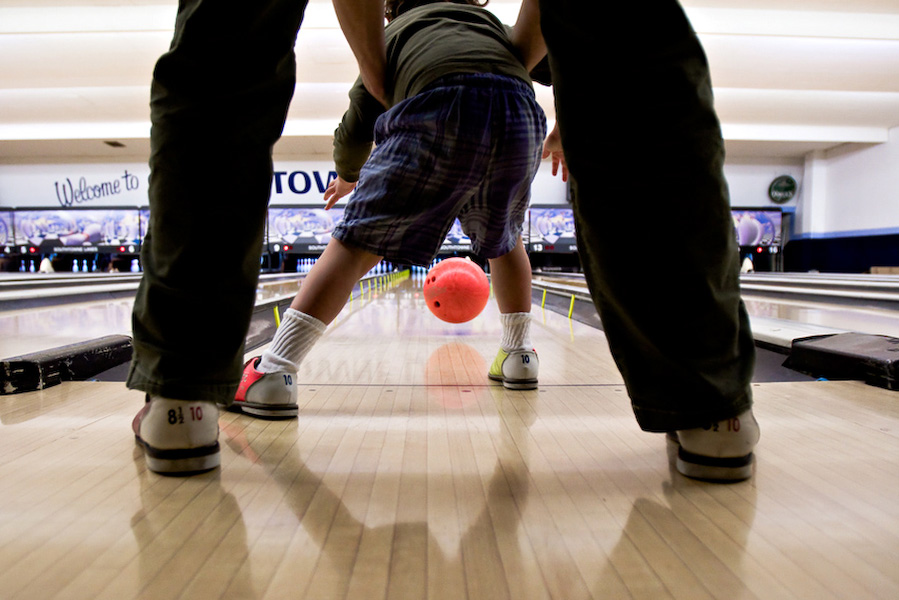 """B's mother helps him bowl during a """"Sign 'n Bowl"""" event put on by the ASL Club at the University of Oregon. """"His grandfather will be so happy to see this,"""" says A, whose father is an avid bowler."""