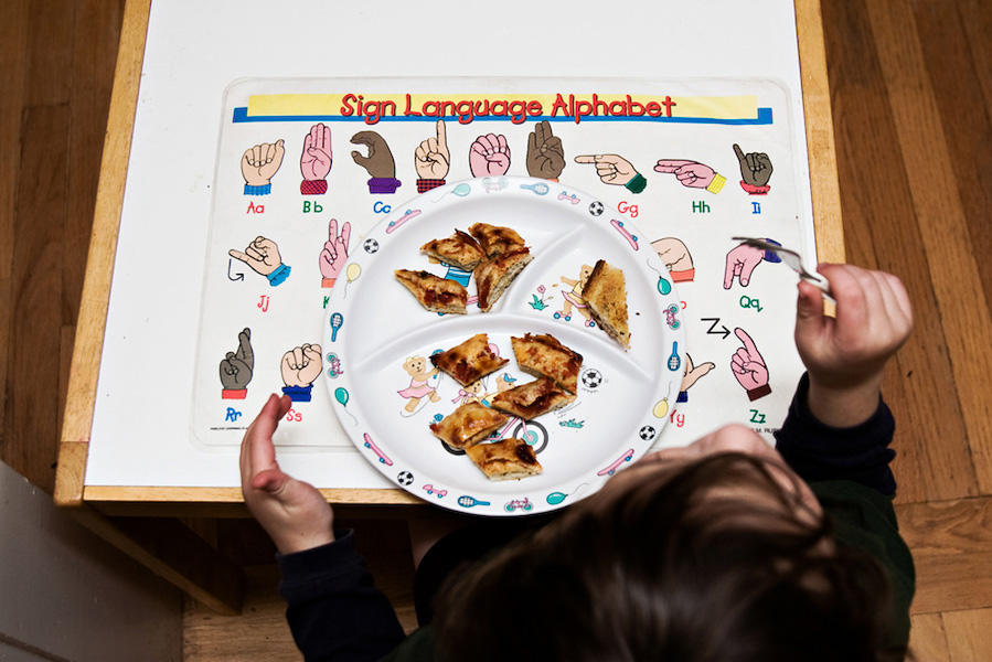 B eats dinner over a sign language placemat, just one of many ASL-themed items in the family's home.