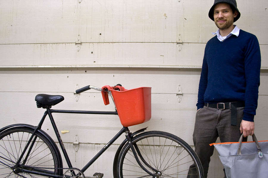 John stands with his Dutch bicycle and self-designed bike bucket and bag. The bucket was a purchase from a farm store and the bag was something he designed and sewed himself. John likes to see the bag as an extension of his desire to solve problems elegantly and simply.
