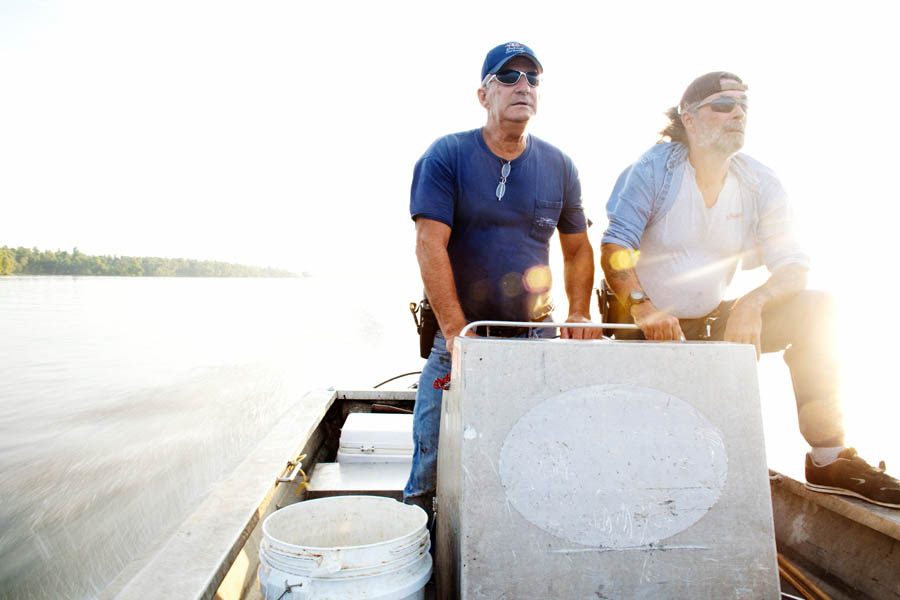 Julius Gaudet, 62, (L) and Rebel (R) glide over the tranquil surface early in the morning as they begin their day hunting for alligators near Shell Island, Louisiana on September 19, 2009.